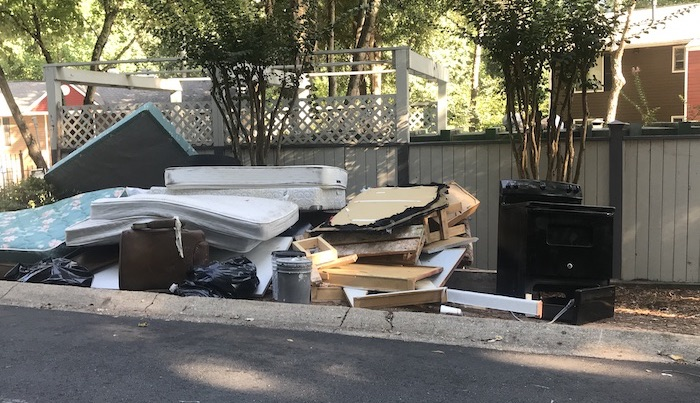 Pile of old furniture in front of dumpster.