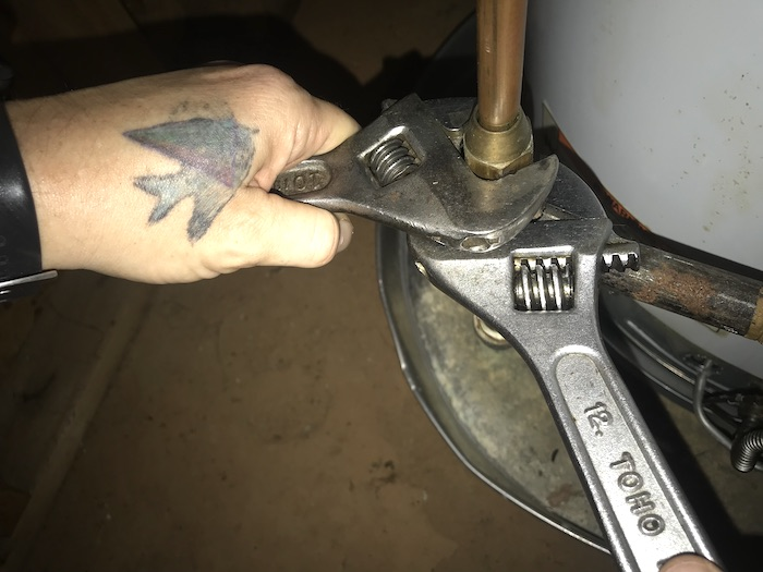 Hands using two wrenches to disconnect gas supply from hot water heater control valve