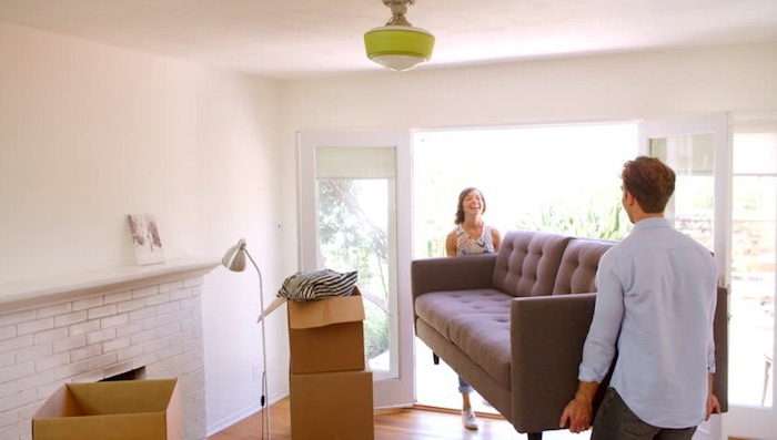 couple laughing carrying gray loveseat out of living room