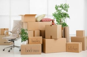group of stacked and labeled moving boxes in a room