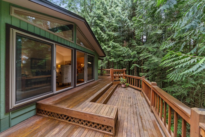 Big brown deck with green trees and a green home
