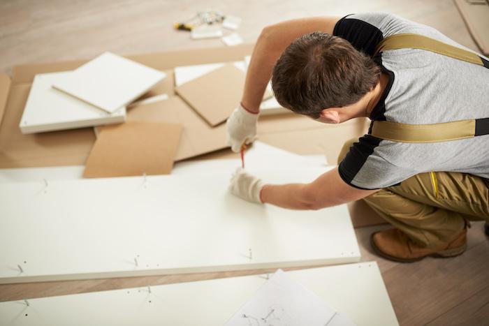 Professional carefully assembling furniture.